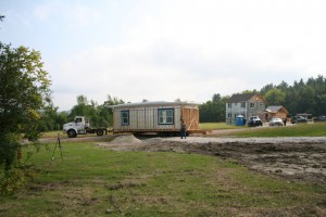 A module for the second high efficiency home being delivered. The first high efficiency modular home is in the background. Photo courtesy of Kika McArthur.