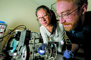 Researchers Richard Lunt and Yimu Zhao test cutting-edge transparent solar cells at their Michigan State University lab. Credit: G.L. Kohuth, The State News.