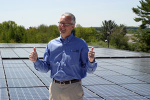 "David Greer, with the rooftop solar system on his company, Wirebelt of America, says ""I just love the stuff!"" Image from Green Energy Times, December 2013."